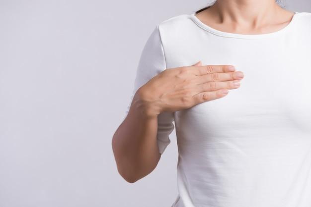 Mano della donna che controlla i grumi sul suo seno per i segni di cancro al seno.