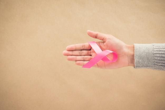 Mano della donna che dà un nastro di raso rosa, simbolo di sostegno della campagna di sensibilizzazione sul cancro al seno in ottobre,