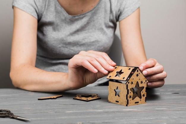 Mano della donna che fa casa piccola creativa sulla tavola di legno