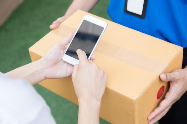 Mano della donna che firma in telefono cellulare con l'accettazione di una consegna delle scatole dal fattorino