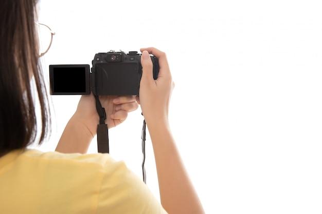 Mano della donna che fotografa con una fotocamera digitale isolata su bianco.
