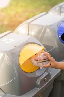 Mano della donna che getta il vetro di plastica nel recipiente di riciclaggio