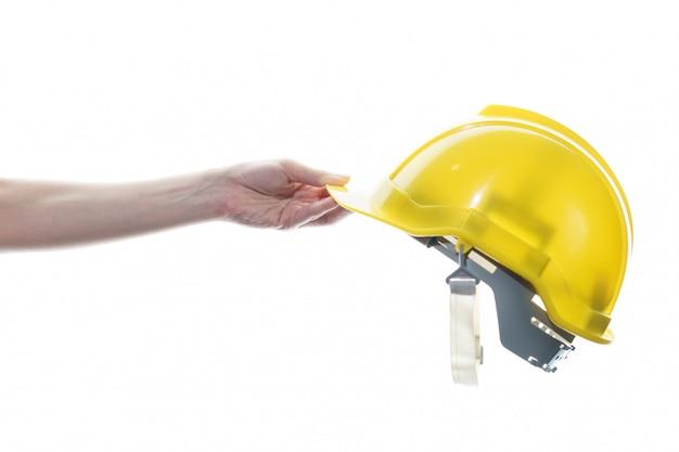 Mano della donna che giudica il casco di sicurezza giallo isolato sulla parete bianca