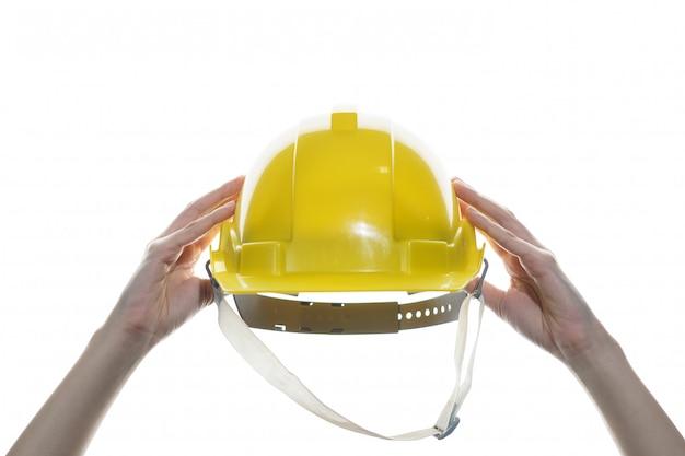 Mano della donna che giudica il casco di sicurezza giallo isolato.