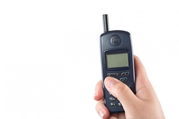 Mano della donna che giudica vecchio telefono cellulare isolato su bianco