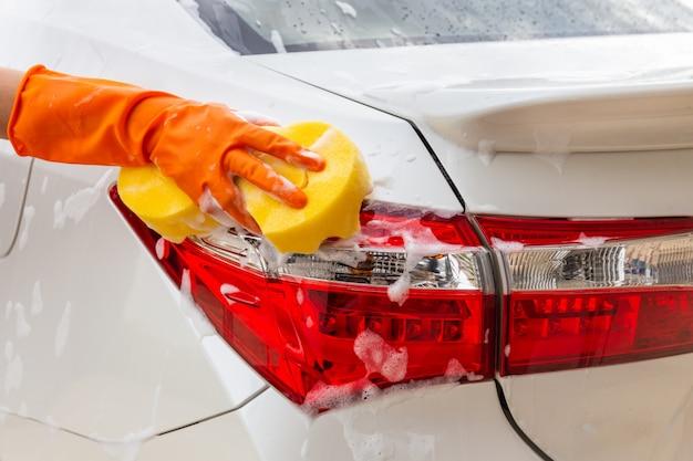 Mano della donna che indossa i guanti arancio con l'automobile moderna del fanale posteriore di lavaggio della spugna gialla