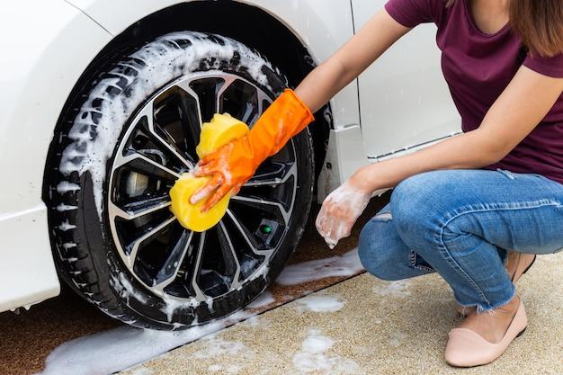 Mano della donna che indossa i guanti arancio con l'automobile moderna della ruota gialla di lavaggio della spugna