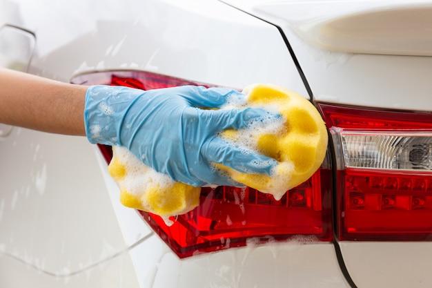 Mano della donna che indossa i guanti blu con l'automobile moderna del fanale posteriore di lavaggio della spugna gialla