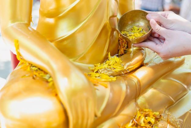 Mano della donna che innaffia la statua del buddha