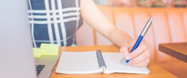 Mano della donna che lavora ad un computer e che scrive su un blocco note con una penna nell'ufficio insegna di web.