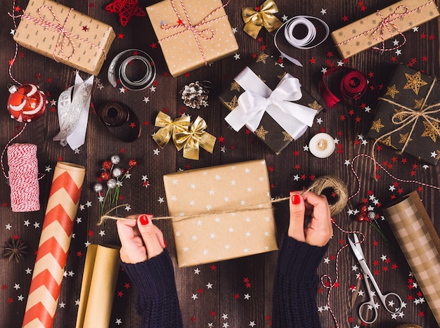 Mano della donna che lega arco con spago per imballare il contenitore di regalo di natale