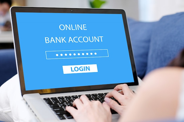 Mano della donna che lega il computer portatile con l'accesso di parola d'ordine del conto bancario online sullo schermo a casa