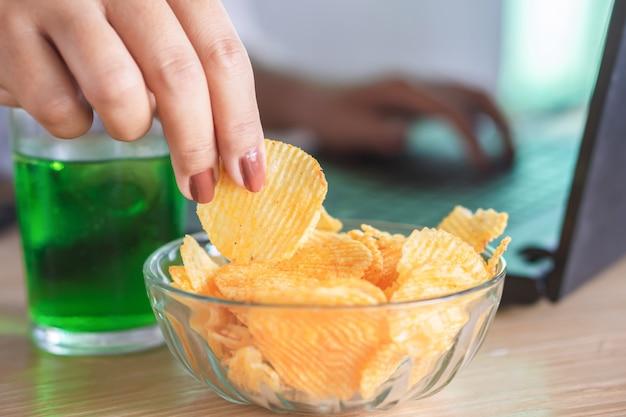 Mano della donna che mangia le patatine fritte all'ufficio