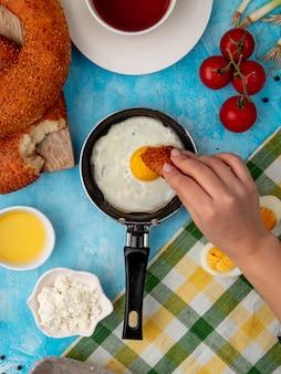 Mano della donna che mangia pane con l'uovo fritto
