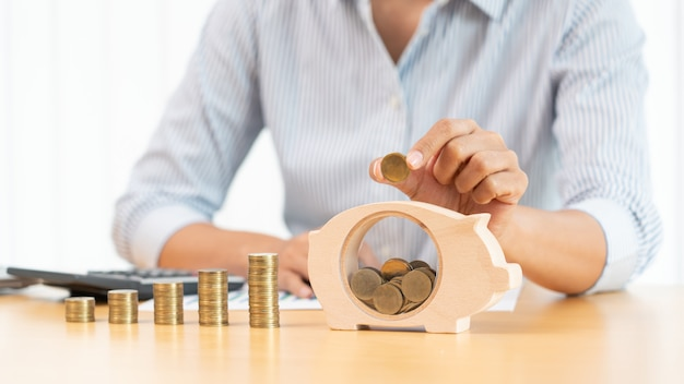 Mano della donna che mette i soldi moneta nel salvadanaio con il passo di crescente pila di monete per risparmiare denaro per il futuro concetto di investimento