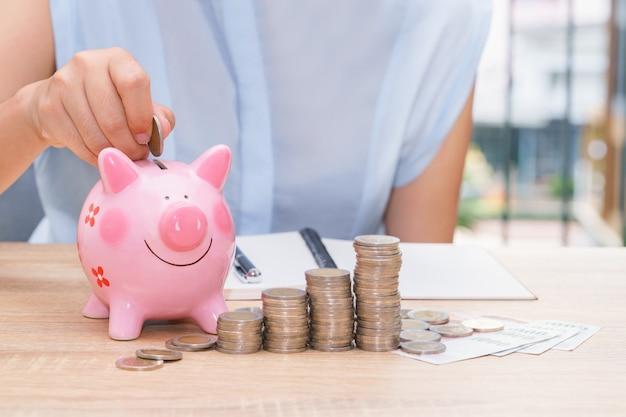 Mano della donna che mette una moneta in un porcellino salvadanaio rosa