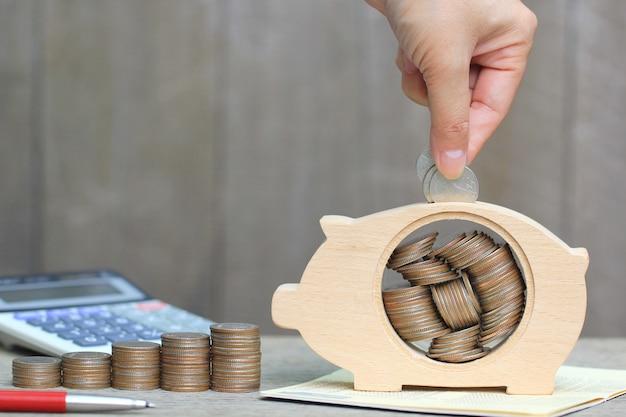 Mano della donna che mette una moneta nel legno del porcellino salvadanaio