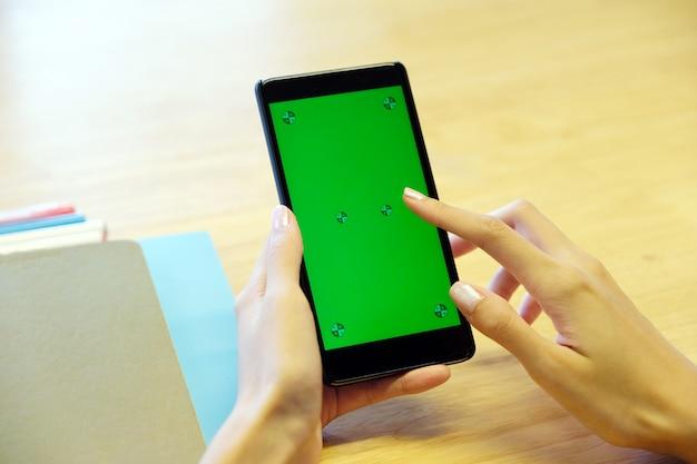 Mano della donna che per mezzo dello smart phone con lo schermo in bianco, l'affare e la tecnologia, internet delle cose