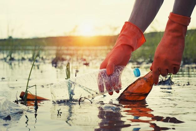 Mano della donna che prende la plastica dell'immondizia per la pulizia al fiume con il tramonto