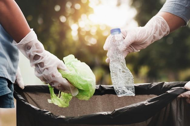 Mano della donna che prende la plastica dell'immondizia per la pulizia al parco