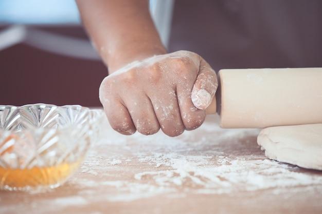 Mano della donna che prepara la pasta di pane per i biscotti bollenti nella cucina nel tono d'annata di colore