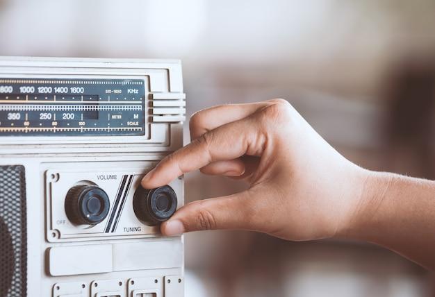 Mano della donna che regola il volume del suono sul retro stereo della cassetta radiofonica nel tono di colore d'annata