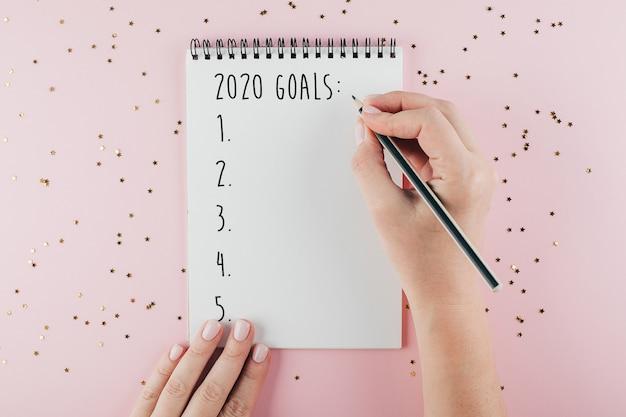 Mano della donna che scrive il taccuino degli obiettivi 2020 decorato con la decorazione di natale