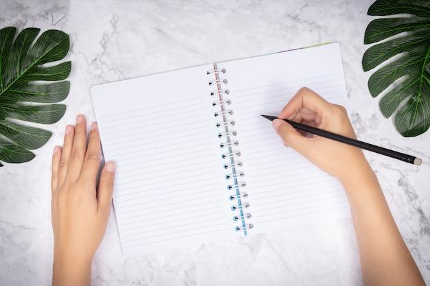 Mano della donna che scrive in un taccuino bianco della pagina bianca sullo scrittorio di marmo bianco