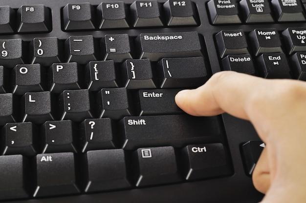 Mano della donna che scrive sulla tastiera di computer nera isolata sopra fondo bianco