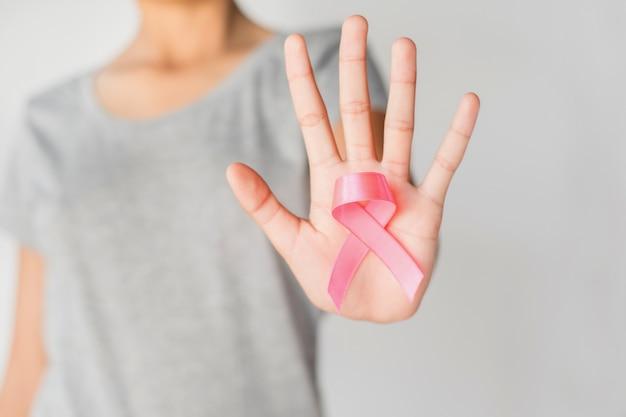 Mano della donna che tiene consapevolezza rosa del cancro al seno del nastro. concetto di assistenza sanitaria e medicina