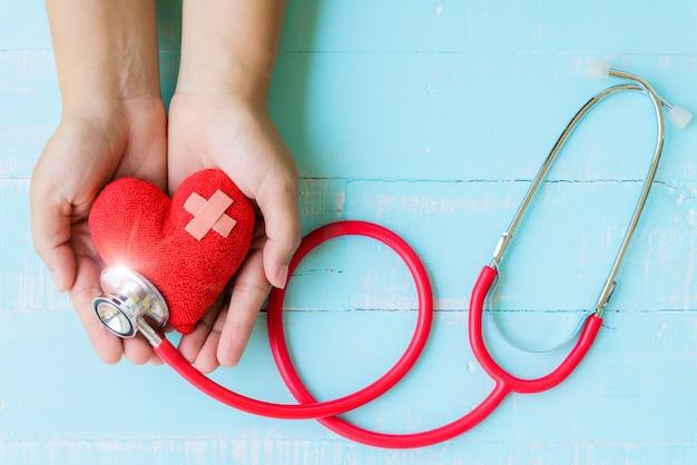Mano della donna che tiene cuore rosso con lo stetoscopio sulla tavola di legno blu