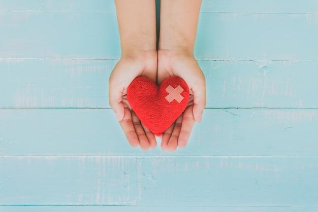 Mano della donna che tiene cuore rosso su fondo di legno blu