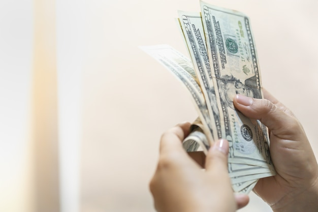 Mano della donna che tiene e che conta la banconota del dollaro americano con lo spazio della copia.