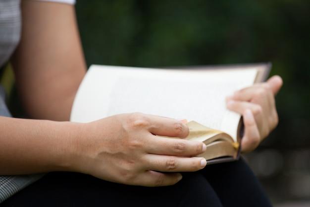 Mano della donna che tiene e che legge un libro nel parco naturale