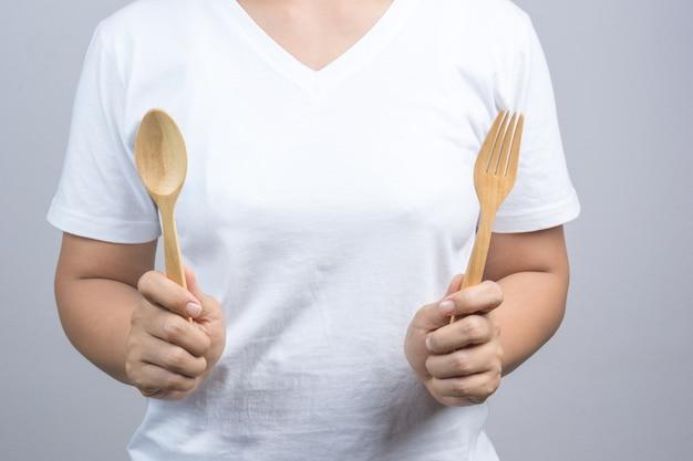Mano della donna che tiene forchetta e cucchiaio di legno