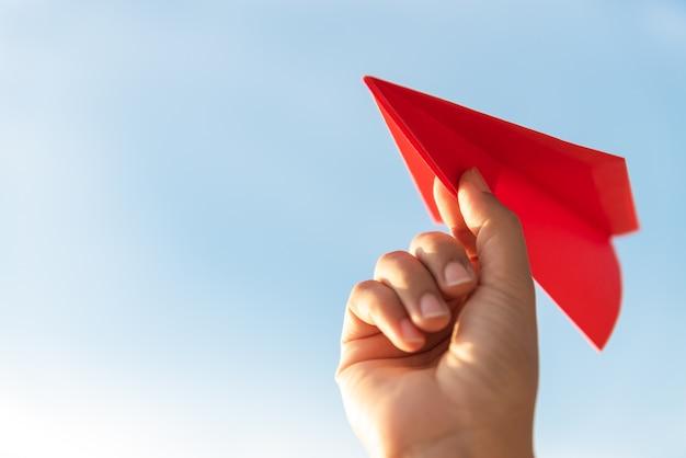 Mano della donna che tiene il razzo di carta rosso con la priorità bassa del cielo blu. concetto di libertà.