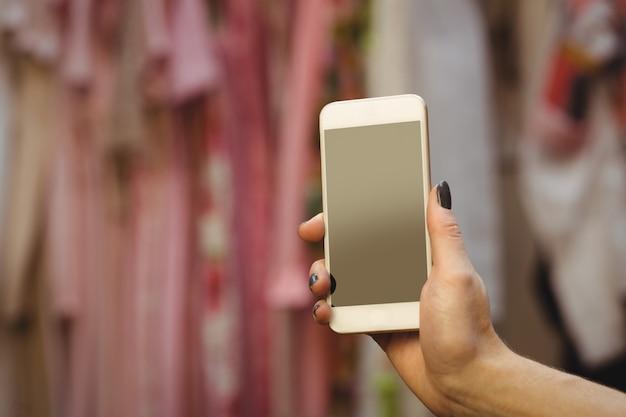 Mano della donna che tiene il telefono cellulare