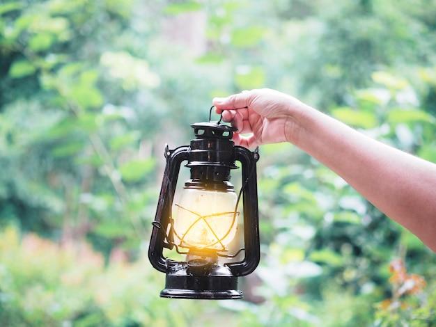 Mano della donna che tiene la vecchia lampada nella foresta.