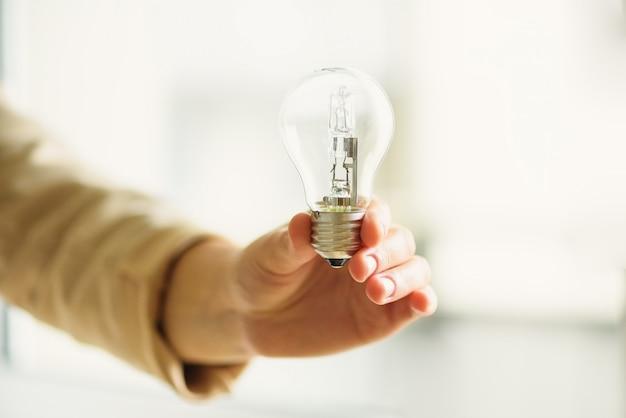 Mano della donna che tiene lampadina su priorità bassa crema con lo spazio della copia. idea creativa, nuovo piano aziendale, motivazione, innovazione, concetto di ispirazione.