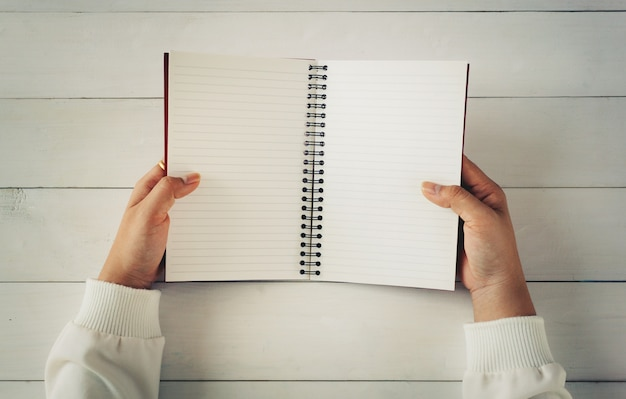 Mano della donna che tiene libro aperto vuoto sulla tavola di legno bianca.