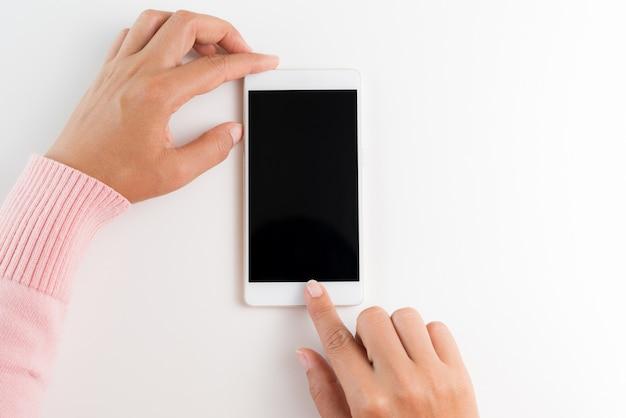 Mano della donna che tiene lo smartphone bianco del telefono cellulare sul fondo bianco della tavola