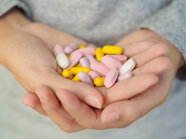 Mano della donna che tiene molte pillole differenti. assistenza sanitaria e concetto medico.