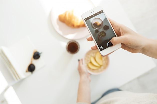 Mano della donna che tiene pollice sullo schermo, sparando al cibo. fotografia di cibo.
