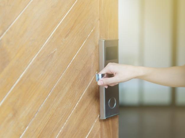 Mano della donna che tiene serratura di porta digitale, manopola di porta digitale con porte in legno chiaro all'interno.