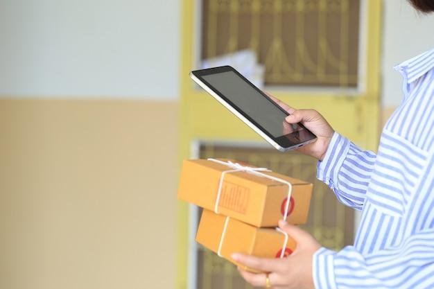 Mano della donna che tiene smart phone e tracciamento pacco online per aggiornare lo stato con ologramma