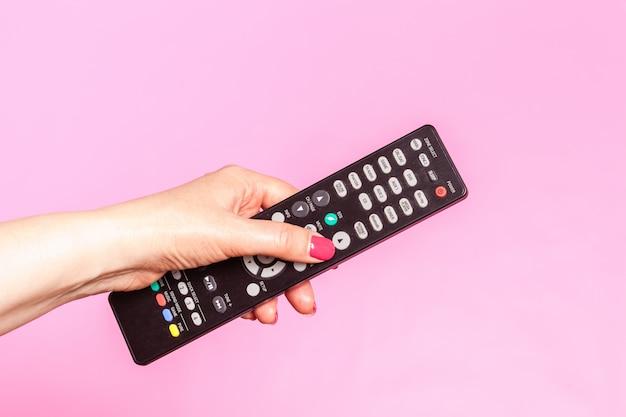 Mano della donna che tiene telecomando, su fondo rosa