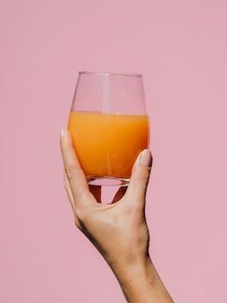 Mano della donna che tiene un bicchiere di succo saporito