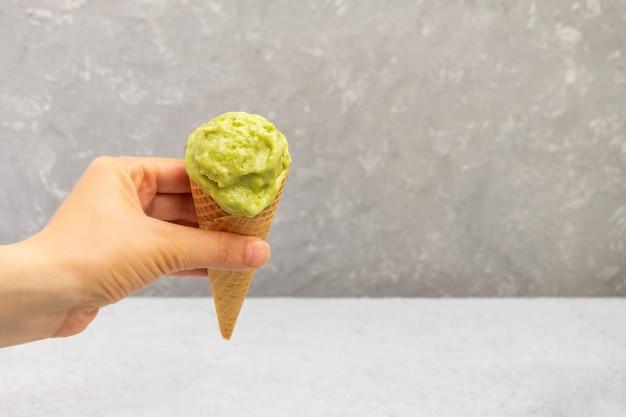 Mano della donna che tiene un cono di cialda con gelato di avocado fatto in casa sano