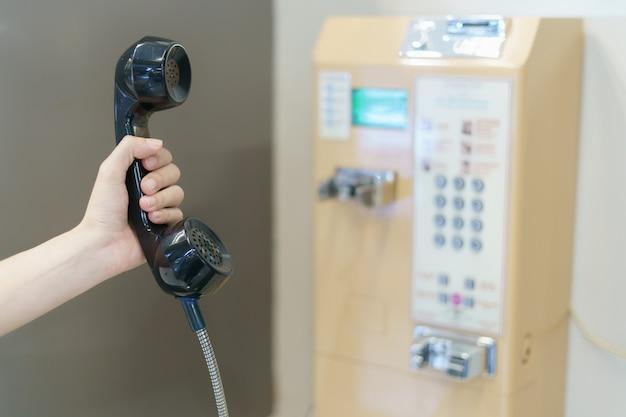 Mano della donna che tiene un telefono di paga della moneta del telefono pubblico