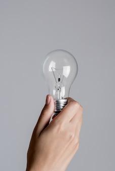 Mano della donna che tiene una lampadina su fondo bianco